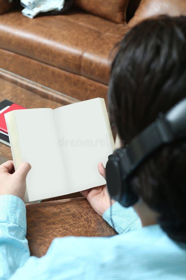 Mann hält offenes Buch in der Hand und hörende Musik mit Kopfhörer stockfoto