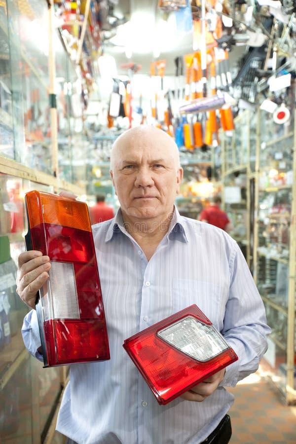 Mann hält Scheinwerfer im Autoteilspeicher an stockbilder