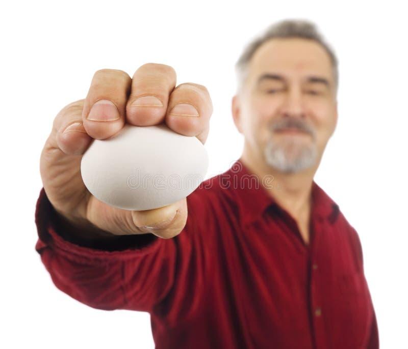 Mann hält weißes Ei in seiner ausgestreckten Hand an. stockfotografie