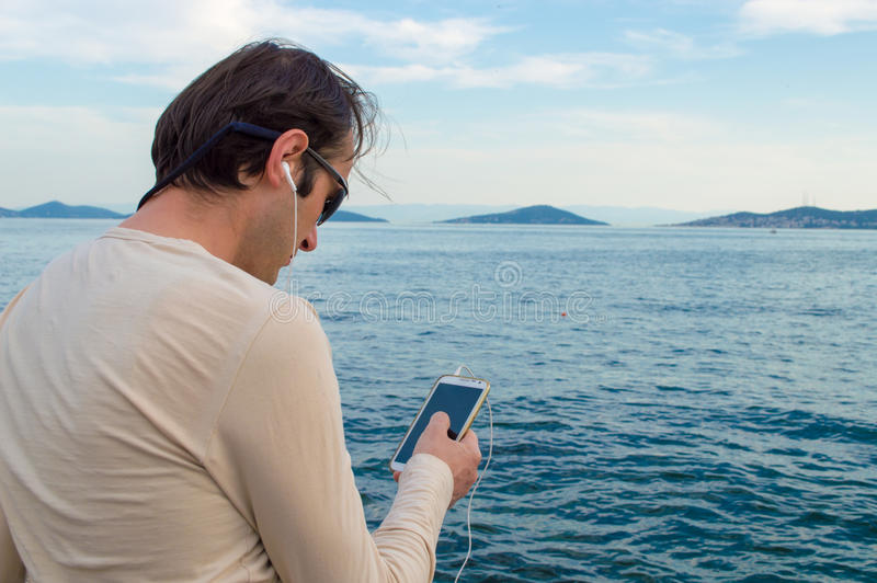 Mann-hörende Musik am Telefon stockbilder