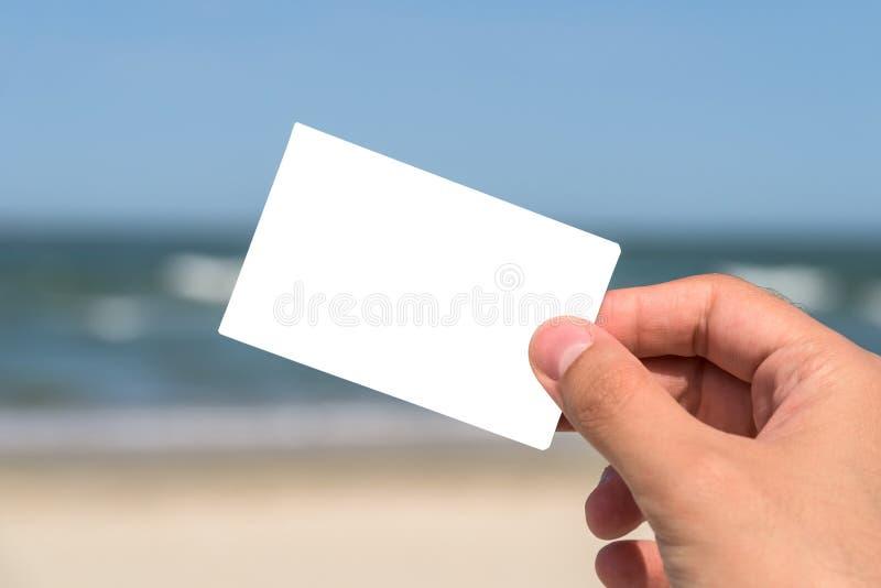 Mann-Hand, die leere weiße Karte hält stockbilder