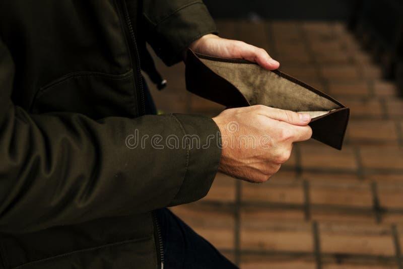 Mann-Handoffene überprüfende leere Geldbörse brach vom Bargeld aus stockfotos