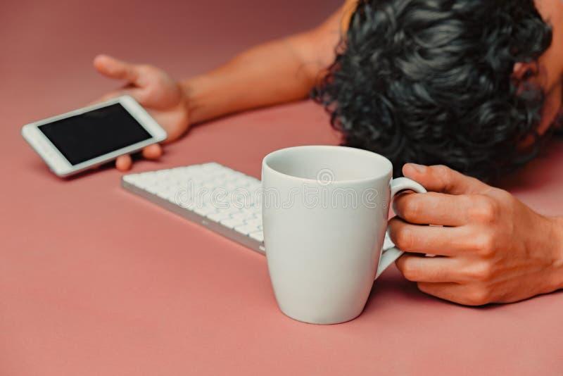 Mann hat ausbrennen bei der Arbeit Kopf, Tastatur, intelligentes Telefon und Kaffee stockfoto