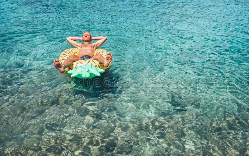 Mann hat, Zeit sich zu entspannen, als Schwimmen auf aufblasbarem Ananaspool schellt stockbilder