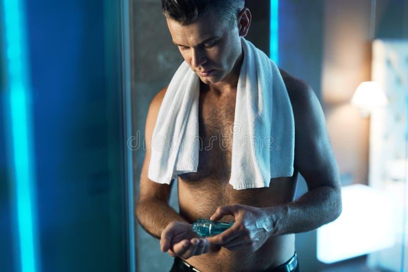 Mann-Hautpflege, nachdem Gesicht rasiert worden ist Mann, der Lotion im Badezimmer verwendet stockbild