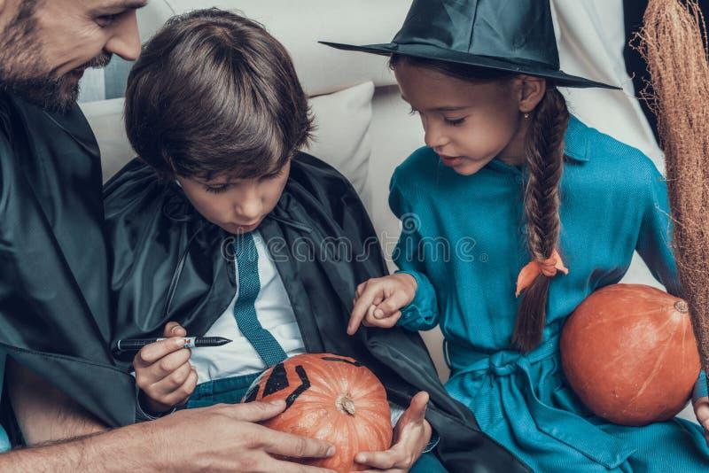 Mann-helfende Kinder in den Kostümen, zum des Kürbises zu schnitzen lizenzfreie stockfotos