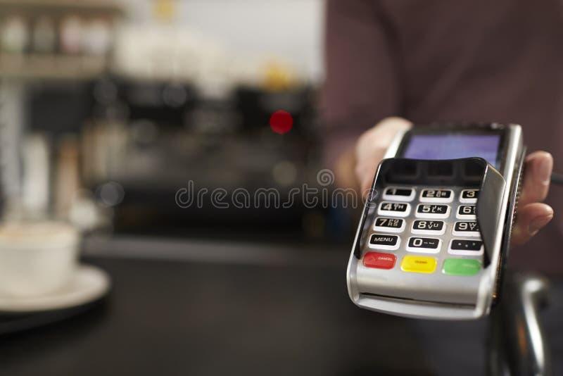 Mann hinter Gegenangeboten Kreditkartenleser, Abschluss des Cafés oben lizenzfreies stockfoto