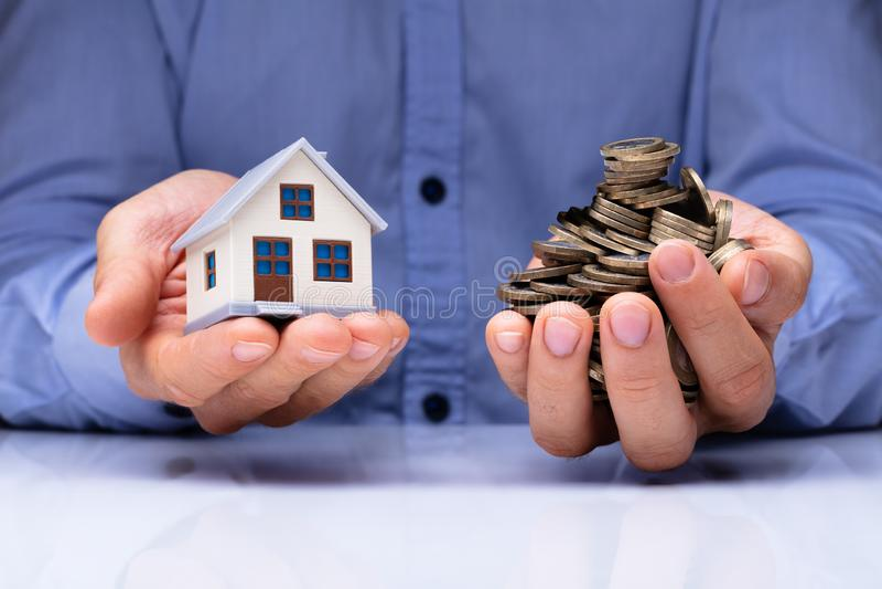 Mann-Holding-Haus-Modell And Coins lizenzfreies stockfoto