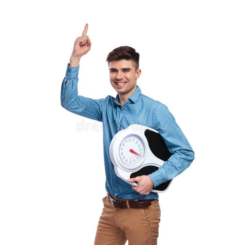 Mann-Holdingskala der glücklichen Junge geeignete und Punktfinger oben stockfoto