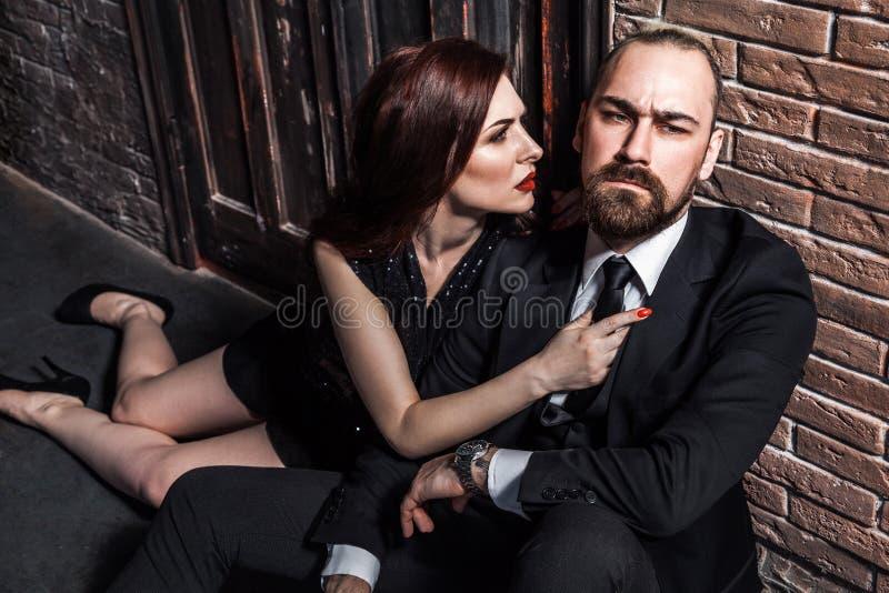 Mann im Anzug und in der Frau im schwarzen Glättungskleid, das auf seinem Schoss sitzt Foxy Frau betrachtet ihn und möchte küssen stockfotos
