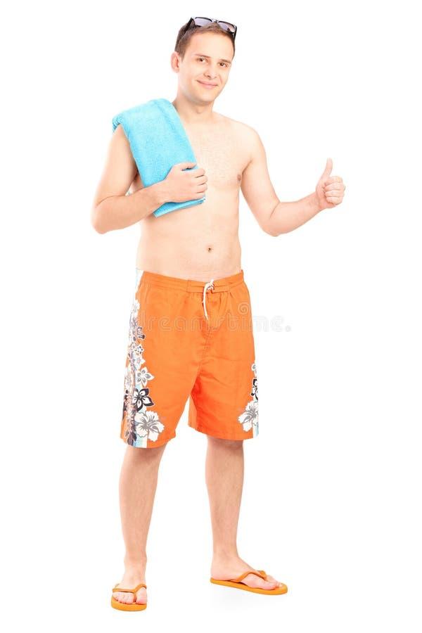 Mann im Badeanzug, der Daumen aufgibt stockfoto