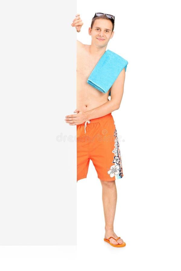 Mann im Badeanzug, der hinter schwarzer Platte steht stockfoto