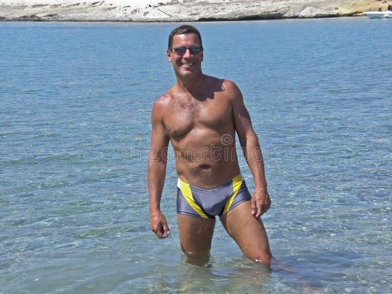 Mann im Badeanzug, der im tropischen Wasser steht stockfotografie