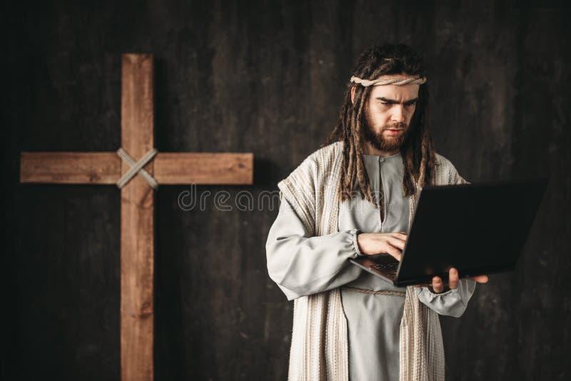 Mann im Bild von Jesus Christ benutzt Laptop lizenzfreie stockfotografie
