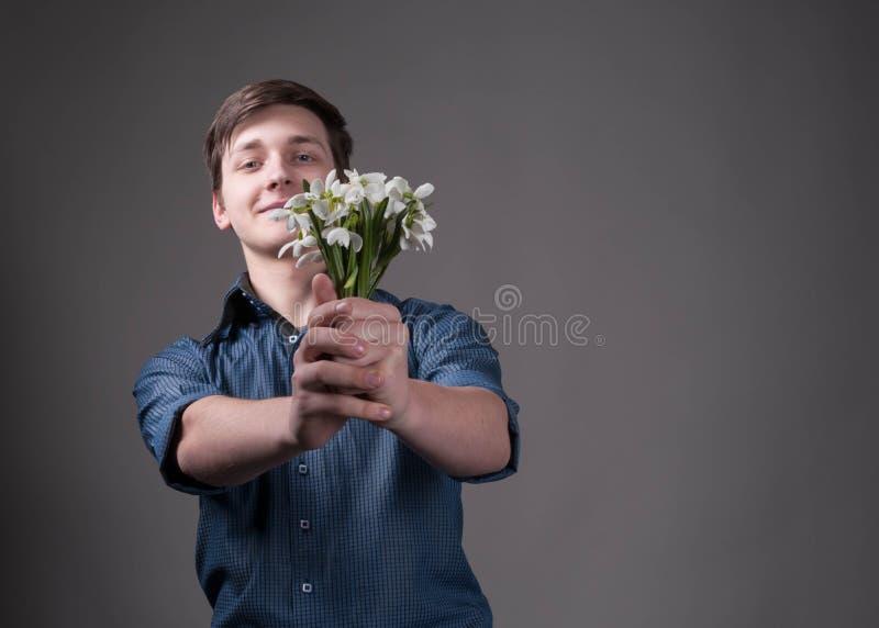 Mann im blauen Hemd, das in ausgestrecktem Handblumenstrauß mit Schneeglöckchen hält und Kamera betrachtet lizenzfreies stockbild