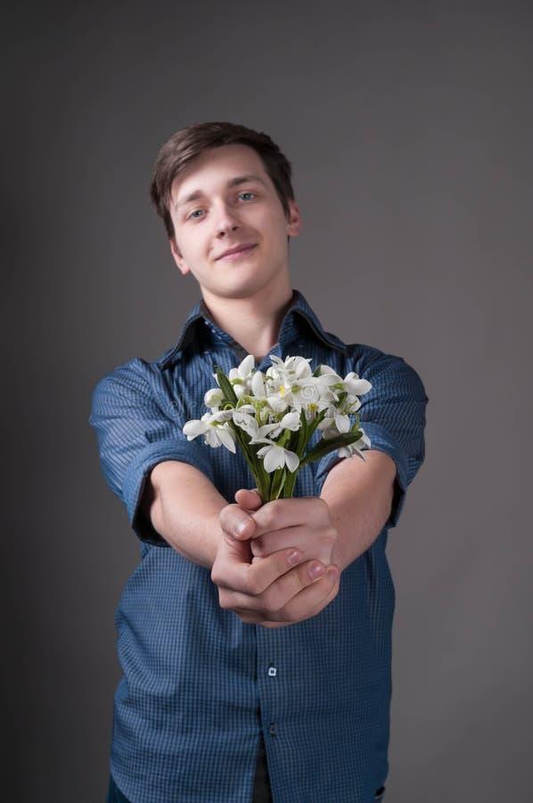 Mann im blauen Hemd, das in ausgestrecktem Handblumenstrauß mit Schneeglöckchen, Kamera und das Lächeln betrachtend hält stockbild