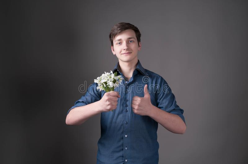 Mann im blauen Hemdholdingblumenstrauß mit den Schneeglöckchen, Kamera betrachtend und greifen oben auf grauem Hintergrund ab lizenzfreie stockfotos