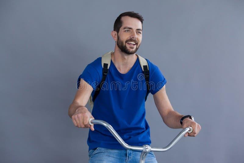 Mann im blauen T-Shirt und in der Rückseite, die das Sitzen auf einem Fahrrad aufwirft stockfoto