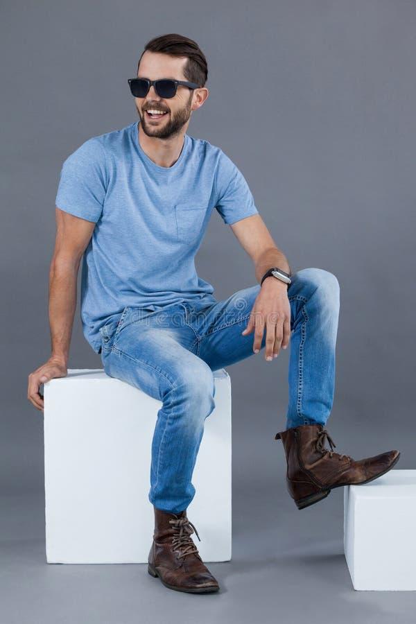 Mann im blauen T-Shirt und in der Sonnenbrille, die auf einem Block sitzt lizenzfreies stockfoto