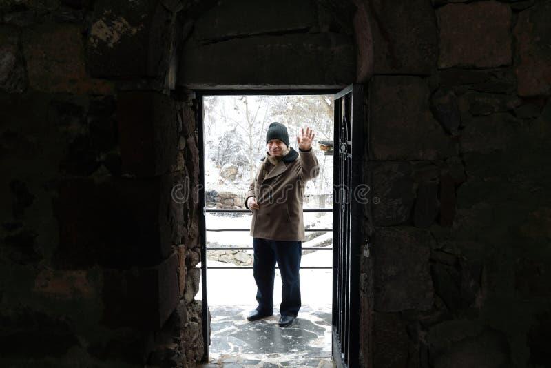 Mann im Eingang in Geghard-Kloster lizenzfreies stockbild