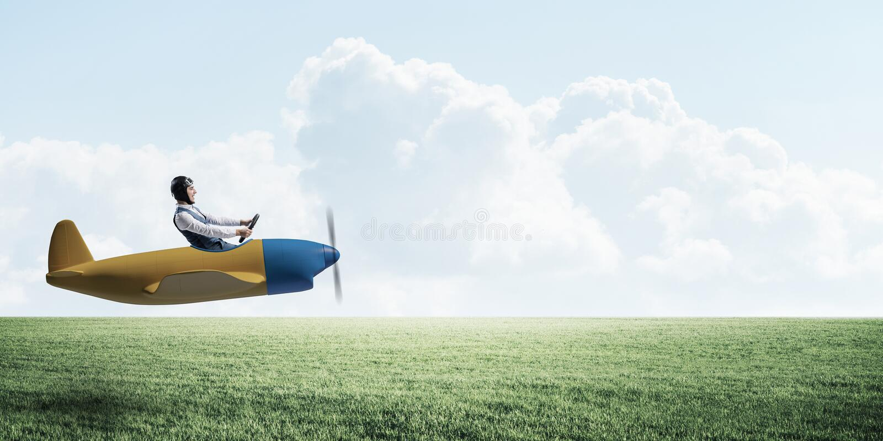 Mann im Flugzeugfliegentief ?ber gr?ner Wiese stockfoto