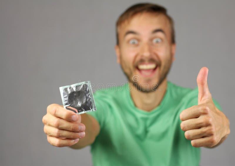 Mann im grünen Hemd hält ein neues Kondom in der Hand, machen Geste thum stockfoto