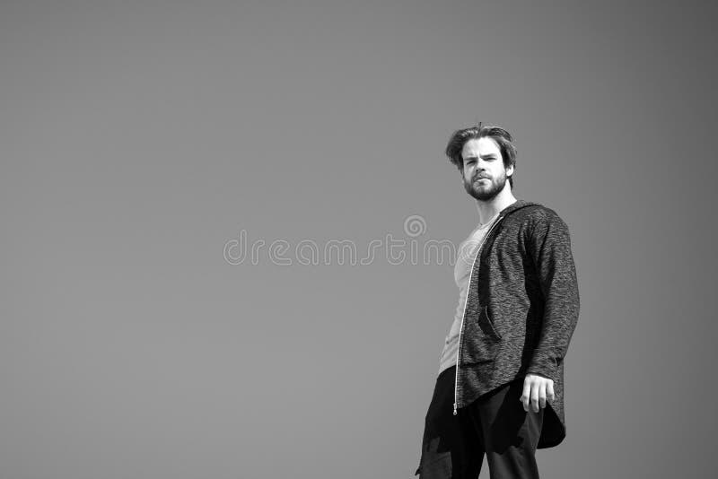 Mann im grauen Mantel, der auf blauem Himmel steht lizenzfreie stockfotografie