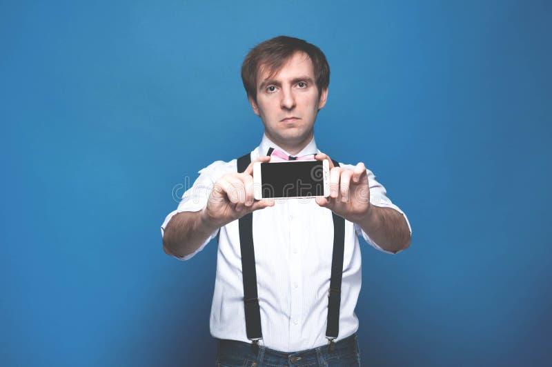 Mann im Hemd und in Hosenträger, die Smartphone mit leerem Bildschirm auf Blau stehen, halten und zeigen stockbilder