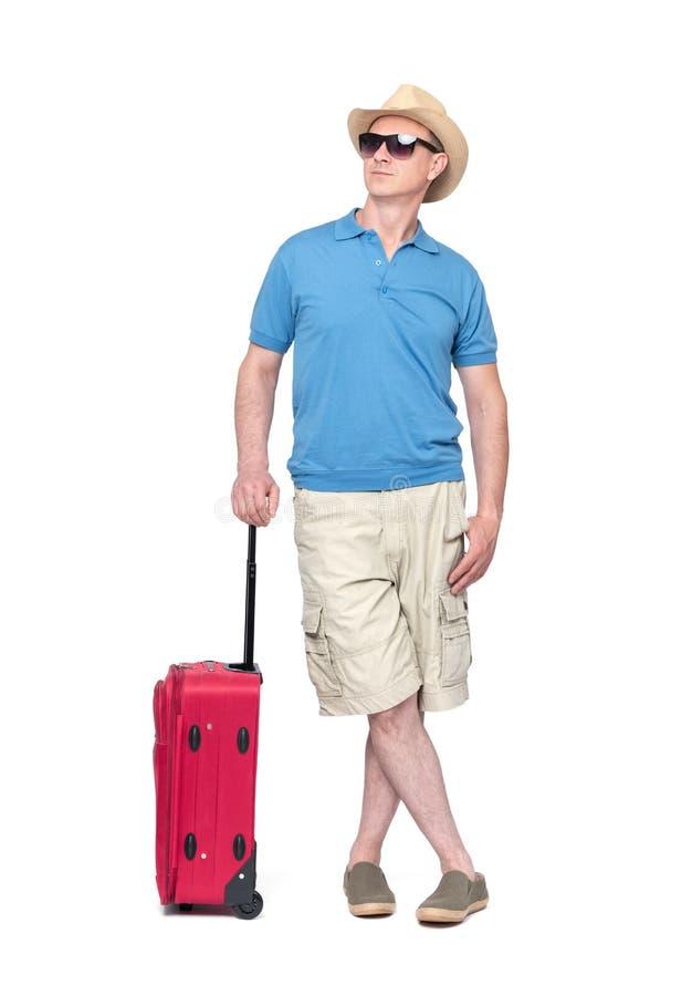 Mann im Hut, in den kurzen Hosen, im T-Shirt und in der Sonnenbrille mit dem roten Koffer, lokalisiert auf weißem Hintergrund Dat lizenzfreies stockfoto