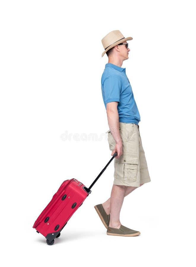 Mann im Hut, in den kurzen Hosen, im T-Shirt und in der Sonnenbrille mit dem roten Koffer, lokalisiert auf weißem Hintergrund Män lizenzfreie stockfotos
