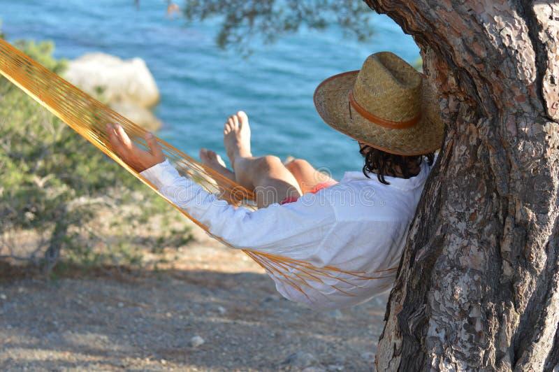Mann im Hut, der in einer Hängematte auf Kiefer in Krim ein Sommersich tag entspannt lizenzfreie stockfotos
