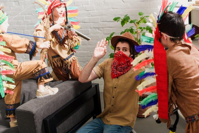 Mann im Hut und in rotem Bandana, die zusammen mit Söhnen in den einheimischen Kostümen spielen stockfoto
