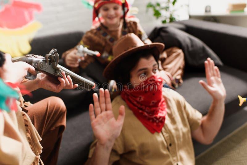 Mann im Hut und in rotem Bandana, die zusammen mit Söhnen in den einheimischen Kostümen spielen stockfotografie