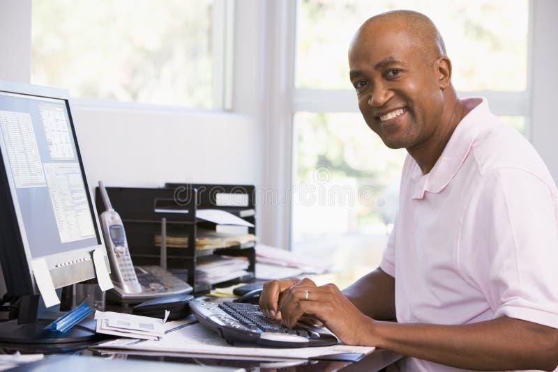 Mann im Innenministerium unter Verwendung des Computers und des Lächelns lizenzfreie stockfotos