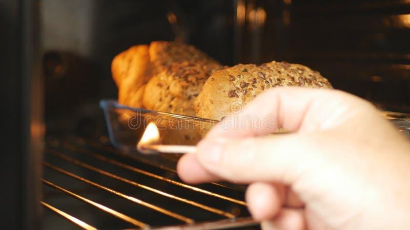Mann im Küchen-Zündungs-Ofen mit Match lizenzfreie stockfotos
