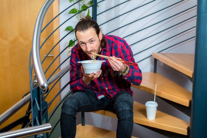 Mann im karierten Hemd, das auf Treppe sitzt und asiatisches Lebensmittel isst lizenzfreies stockfoto