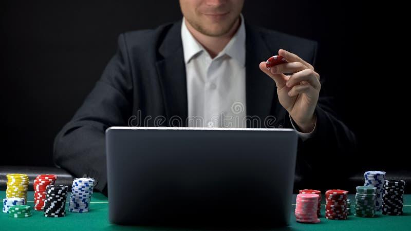 Mann im Klagenspiel online auf Laptop, Kasinochip in der Hand halten und wetten stockfoto