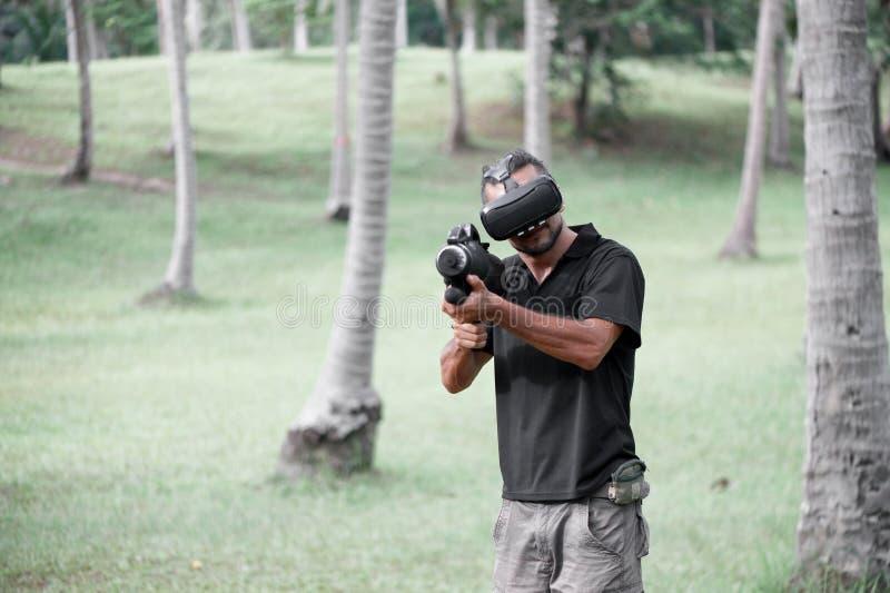 Mann im Kopfhörer der virtuellen Realität, der draußen Videospiel spielt stockfoto