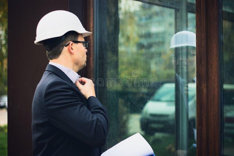 Mann im Kostüm und weißer Sturzhelm überprüfen seinen Blick an der Fensterreflexion lizenzfreies stockfoto