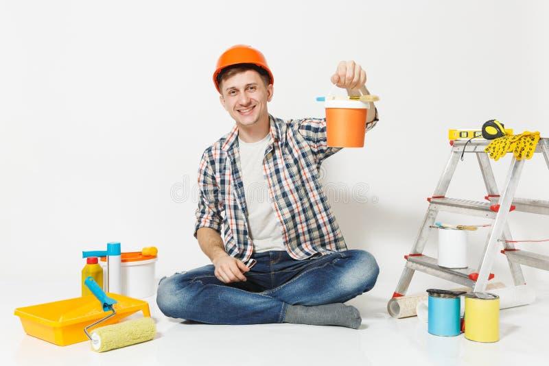 Mann im orange Schutzhelm, der auf Boden mit Farbendose, Instrumente für die Erneuerungswohnung lokalisiert auf Weiß sitzt stockfotos