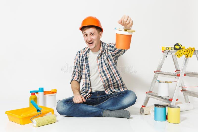 Mann im orange Schutzhelm, der auf Boden mit Farbendose, Instrumente für die Erneuerungswohnung lokalisiert auf Weiß sitzt lizenzfreie stockfotografie