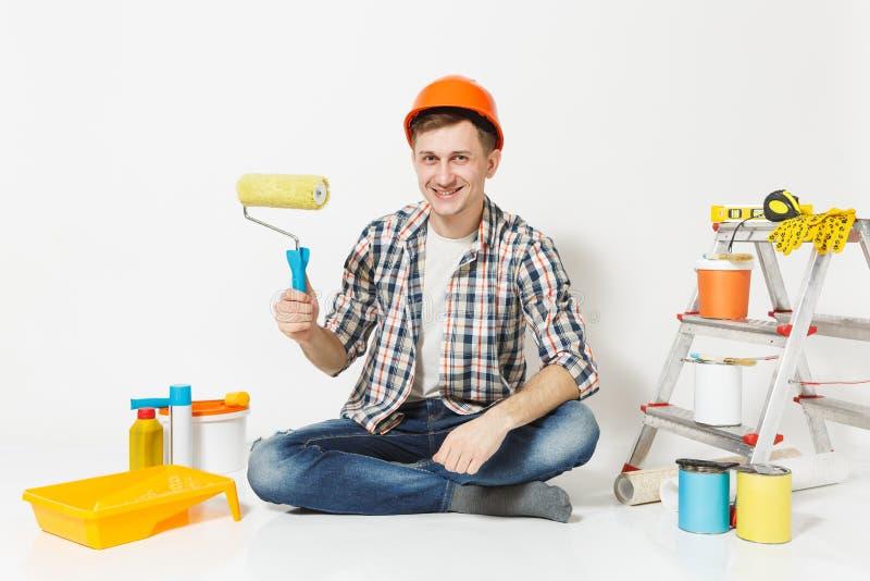 Mann im orange Schutzhelm, der auf Boden unter Verwendung der Farbenrolle sitzt Instrumente für die Erneuerungswohnung an lokalis lizenzfreies stockfoto