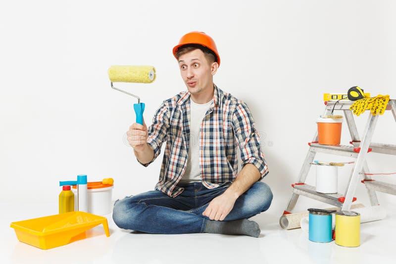 Mann im orange Schutzhelm, der auf Boden unter Verwendung der Farbenrolle sitzt Instrumente für die Erneuerungswohnung an lokalis stockbilder