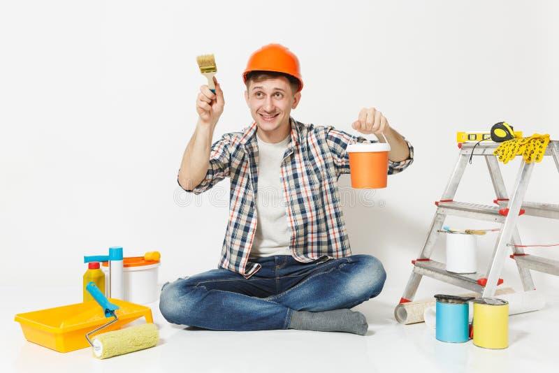 Mann im orange Schutzhelm, der mit Pinsel, Dose, Instrumente für die Erneuerungswohnung lokalisiert auf Weiß sitzt lizenzfreies stockfoto