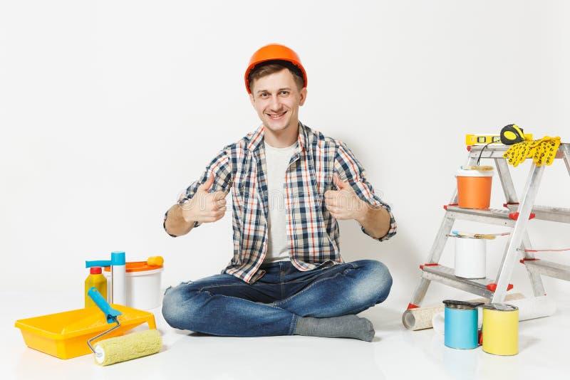 Mann im orange Schutzhelm, der sich Daumen, sitzend auf Boden mit Instrumenten für die Erneuerungswohnung lokalisiert zeigt stockbilder
