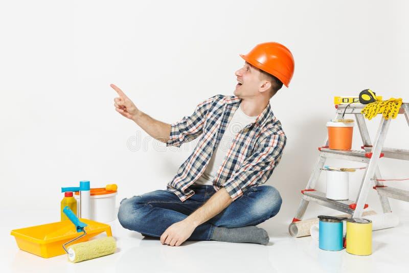 Mann im orange Schutzhelm Zeigefinger auf Kopienraum beiseite zeigend Instrumente für die Erneuerungswohnung lokalisiert stockfoto