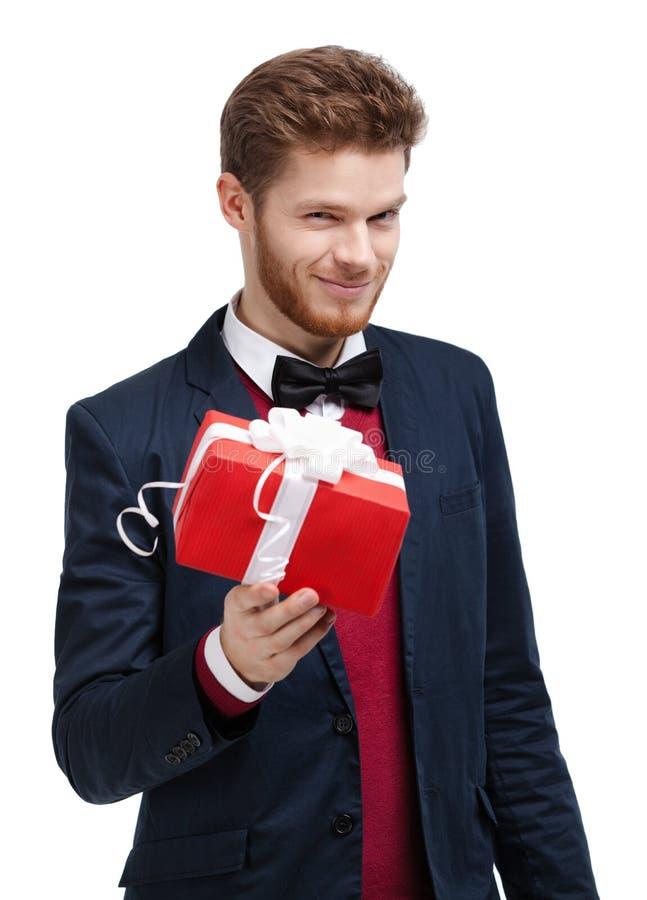 Mann im Querbinder bietet ein Geschenk an stockbild