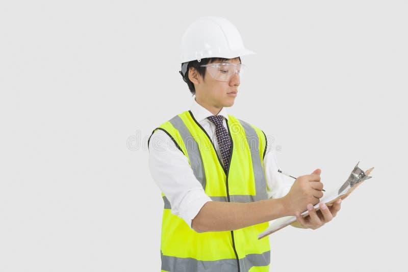 Mann im Reflektorwesten- und -Schutzhelmschreiben auf Klemmbrett im Büro stockbilder