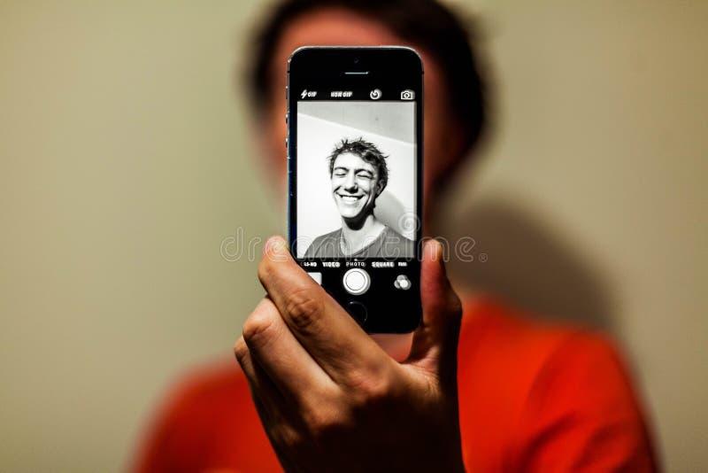Mann im Roten Hemd, der auf seinem iPhone Selfie im Graustufenmodus hatte lizenzfreies stockbild