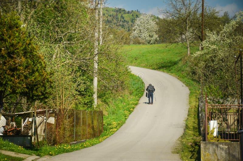 Mann im Ruhestand, der durch Frühlingsdorf auf der Asphaltstraße geht Er hilft sich mit Krücken stockfotos